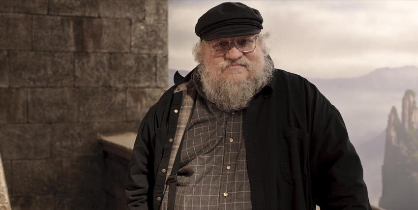 george r.r. martin in posa sopra il camminatoio di un castello - nerdface