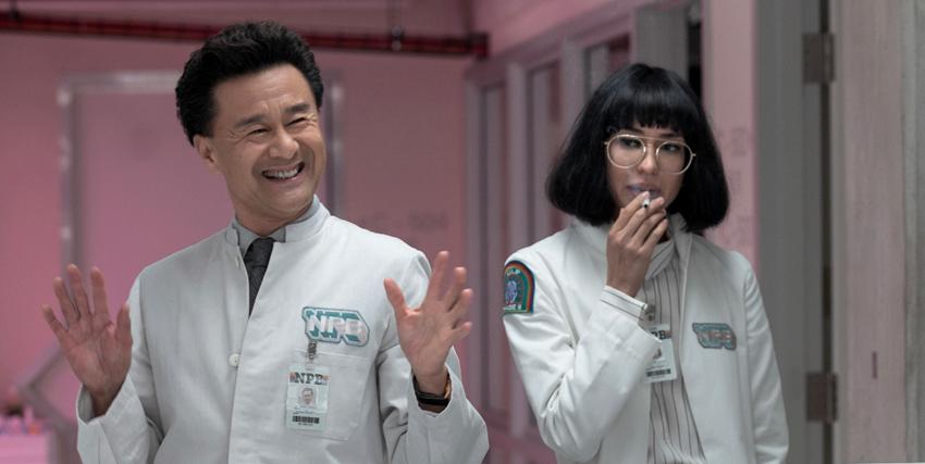 un medico asiatico sorride, mentre una dottressa dal caschetto castano sta fumando una sigaretta - nerdface