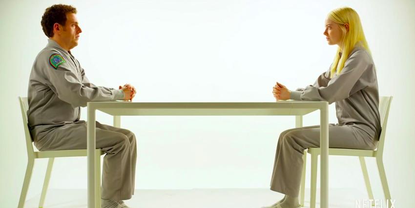 i due protagonisti di maniac si fronteggiano seduti in una camera bianca e su un tavolo di metallo - nerdface
