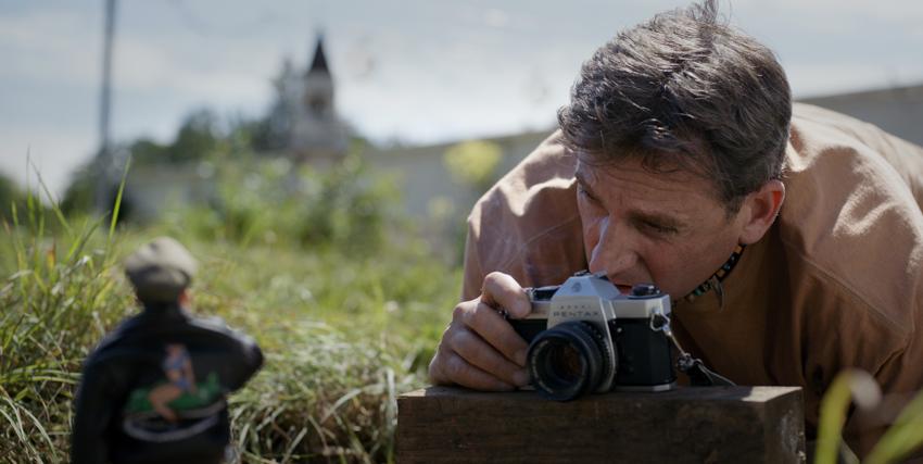 mark hogancampo fotografa il suo modellino in mezzo a un prato - nerdface