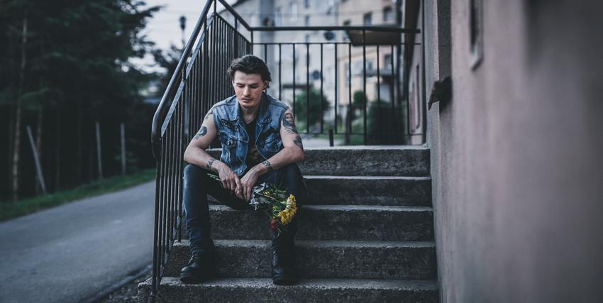 un giovane in gicca jeans smanicata siede sconsolato su alcune scalette - nerdface