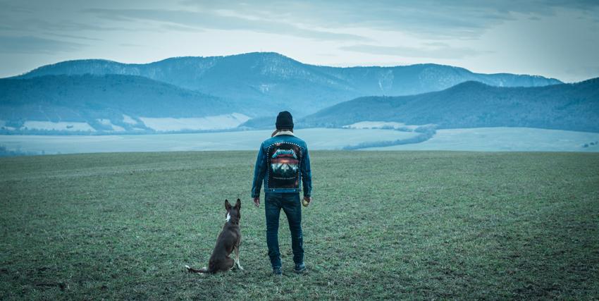 un ragazzo e il suo cane di spalle guardano un panorama mozzafiato fatto di pianura e montagne sullo sfondo - nerdface