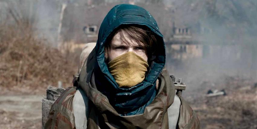 un ragazzo incapucciato e con un pezzo di stoffa a coprire bocca e naso e cammina in una landa desolata - nerdface