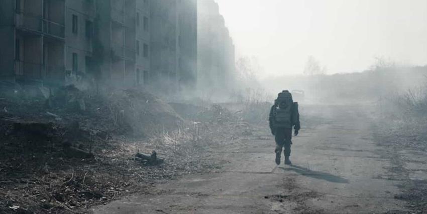 un uomo in quella che sembra una tuta antiradiazioni cammina in una strada nebbiosa - nerdface