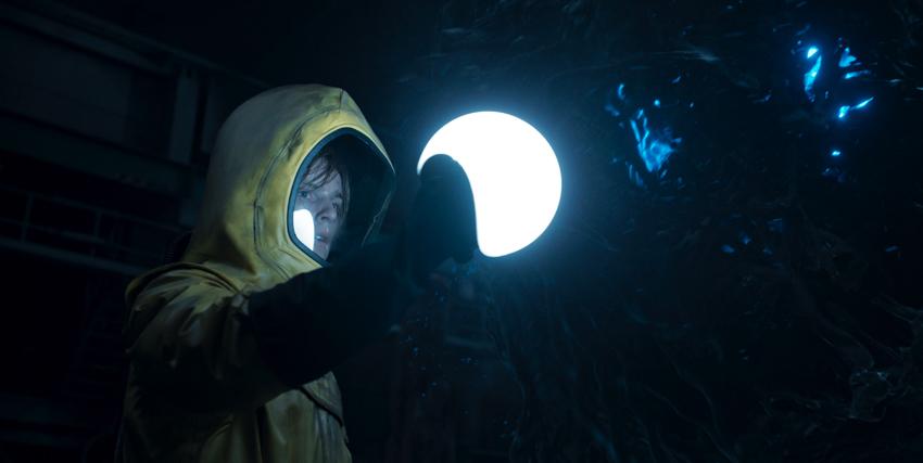 un ragazzo in tuta antiradiazioni gialla ha trovato qualcosa nel buio di una grotta. illuminata solo da un faro - nerdface