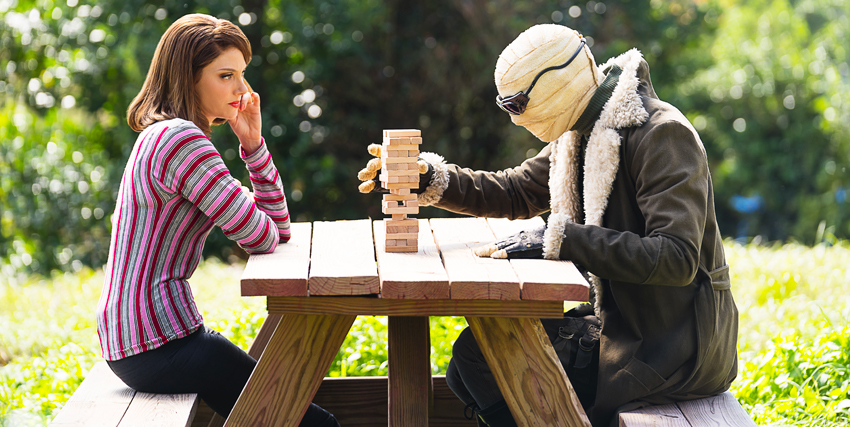 due protagonisti della doom patrol sono seduti a un tavolo e giocano a un gioco con alcuni mattoncini in legno - nerdface