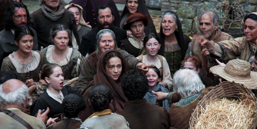 una giovane donna è circondata da un gruppo di persone e additata come strega - nerdface