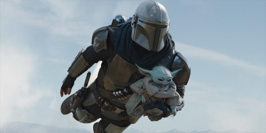 il mandaloriano sta volando e tiene in braccio baby yoda - nerdface
