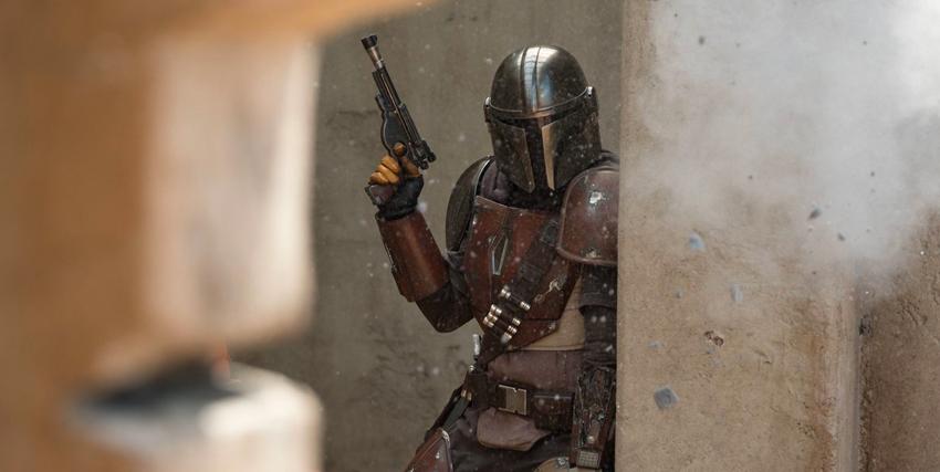 il mandaloriano, pistola in mano, fa capolino da un muro dietro al quale trova riparo - nerdface
