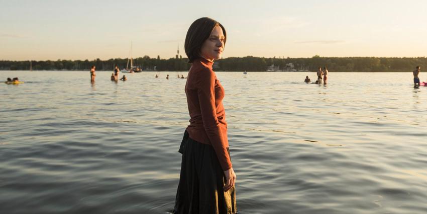 la giovane protagonista è immersa fino alle ginocchia in un lago, mentre è ancora vestita. sorride: qualcosa sta cambiando - nerdface