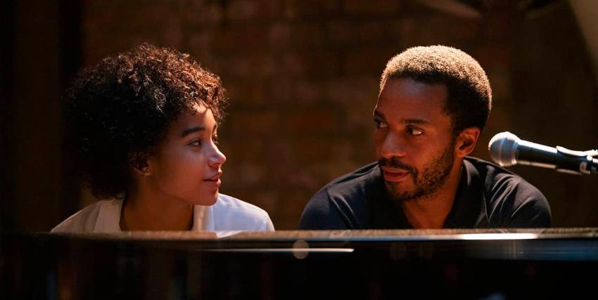 un uomo e una donna si guardano intensamente mentr sono seduti davanti la tastiera di un piano a coda - nerdface
