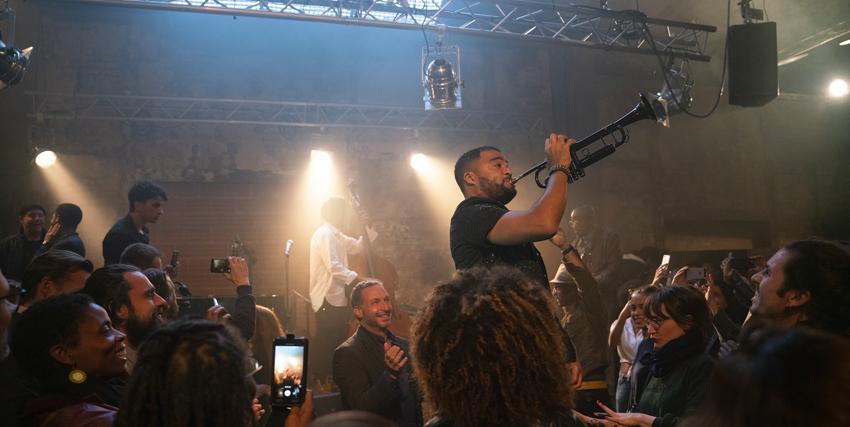 un concerto vede sul palco un trombettista fare un solo, mentre i pubblico ascolta divertito - nerdface