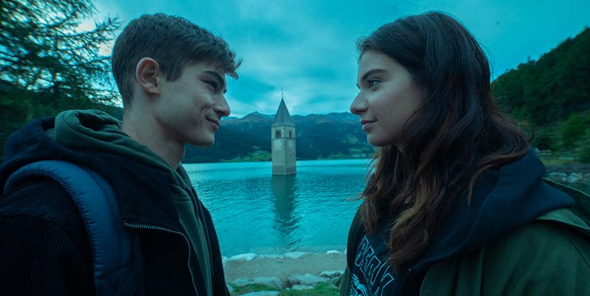 due ragazzi si guardano e sorridono, sullo sfondo il lago dal quale emerge il campanile di una città sommersa - nerdface
