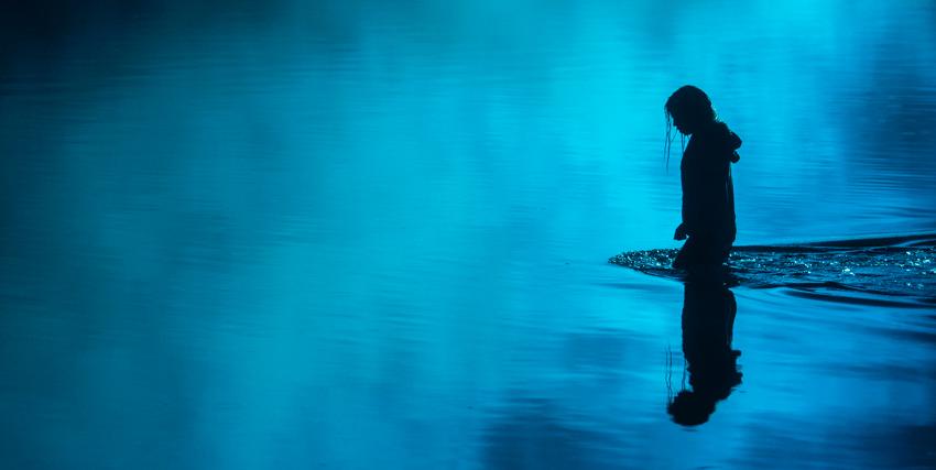 immersa nella nebbia, una donna si sta immergendo vestito nelle acque del lago - nerdface