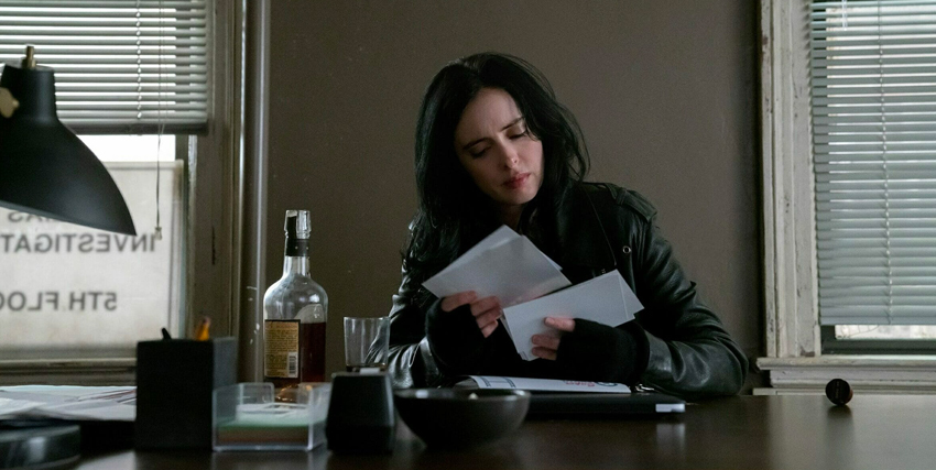 jessica jones legge alcune cate mentre è seduta alla sua scrivania - nerdface