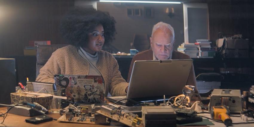 un uomo e una donna sono seduti a una scrivania lavorando al computer - nerdface