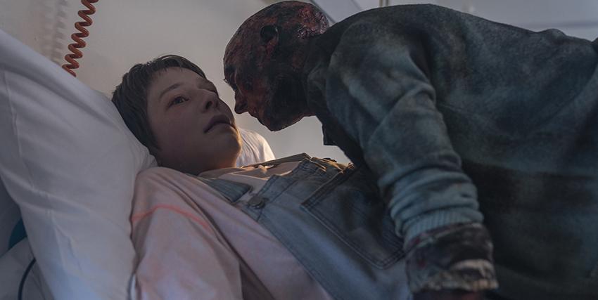 una donna è stesa su un letto, forse in coma, e su di lei si china un uomo che sembra una via di mezzo tra uno zombie e un fantasma - nerdface