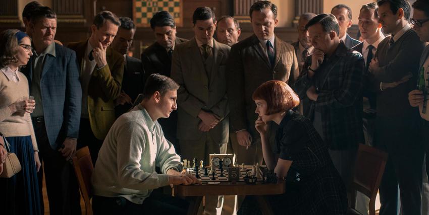 la protagonista sta duellando a scacchi contro un giovane e il loro tavolo è circondato dal pubblico - nerdface