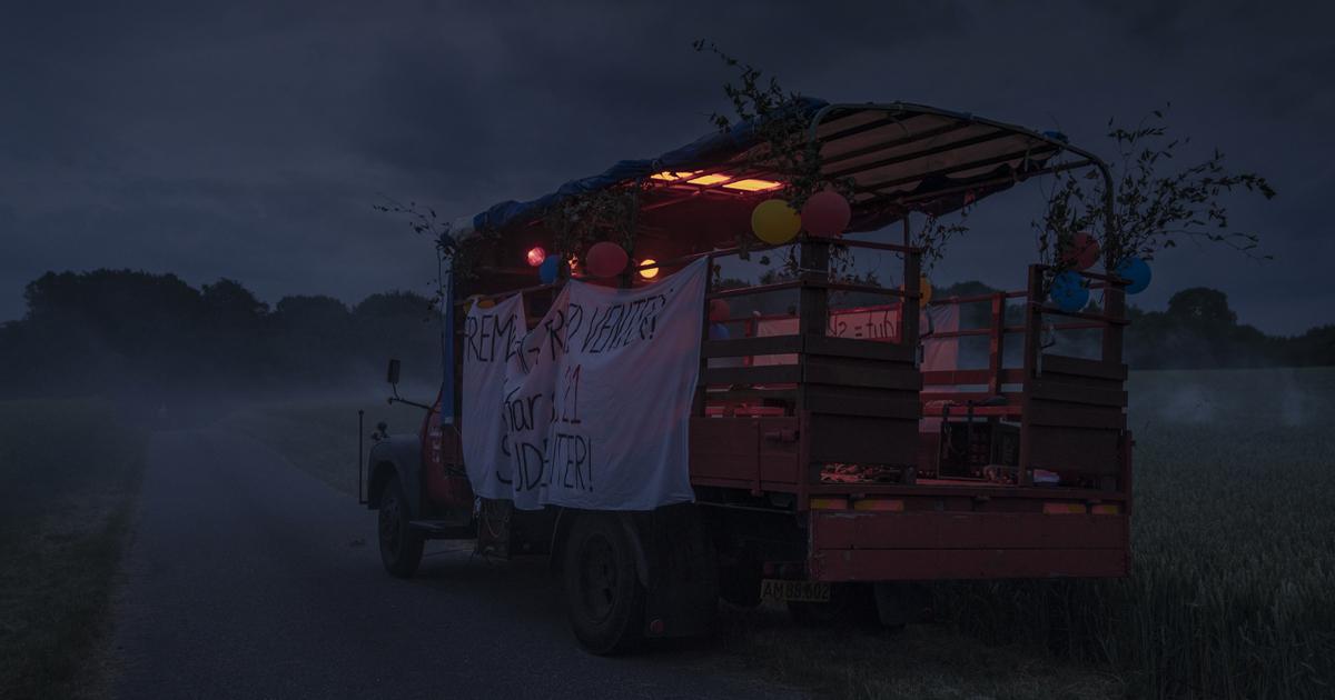 un camion con qualchge anno sulle spalle sta viaggiando di notte e mostra uno striscione sul lato sinistro. in danese, non chiedeteci la traduzione - nerdface