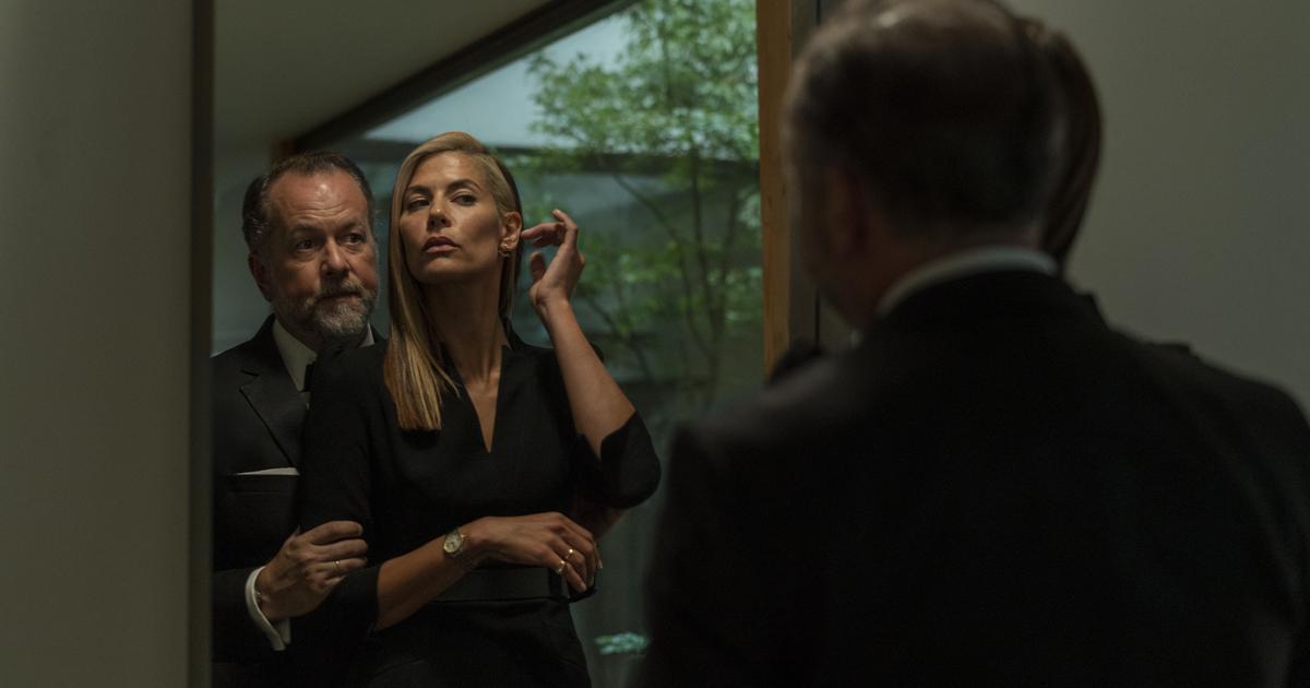 un uomo abbraccia una donna da dietro, entrambi di fronte a uno specchio, mentre lei si aggiusta i capelli dietro l'orecchio sinistro - nerdface