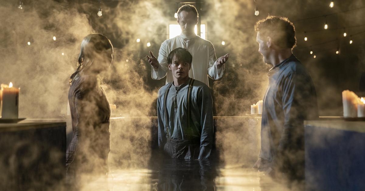 un ragazzo è immerso a metà in una vasca che sembra battesimale. accanto a lui un uomo e una donna, dietro un altro uomo con le mani sollevate a mo' di benedizione - nerdface