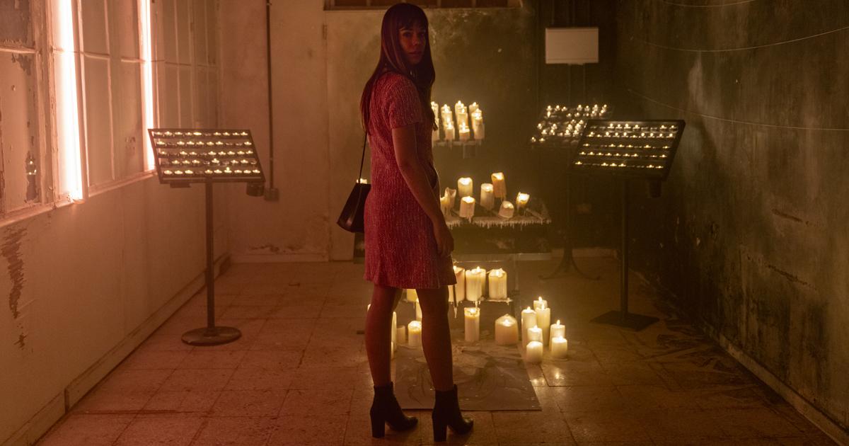 una donna sexy è in una stanza, forse una cripta, piena di candele - nerdface