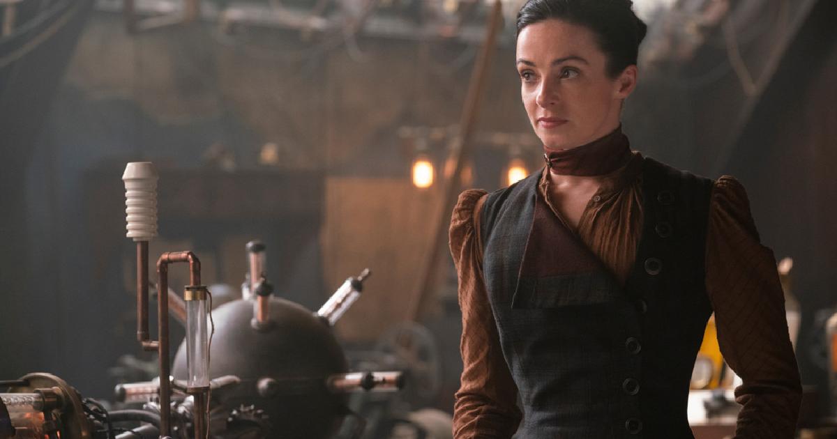 la protagonista sorride in una sala con alcuni macchinari misteriosi - nerdface