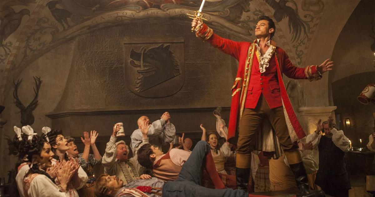 Luke Evans in una scena Disney nei panni di Gaston. In piedi su un tavolo con un pugnale in mano, acclamato dagli abitanti del paese.