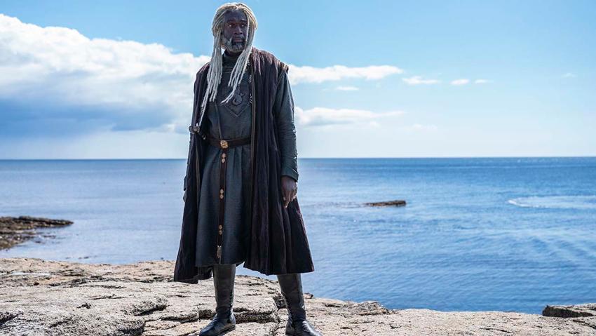 Un personaggio in riva al mare, carnagione scura, capelli bianchi, sguardo fiero.
