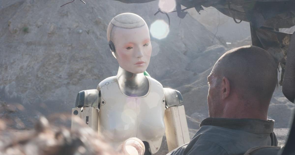 un robot dal volto di donna osserva banderas, steso sui rottaqmi in mezzo al deserto - nerdface
