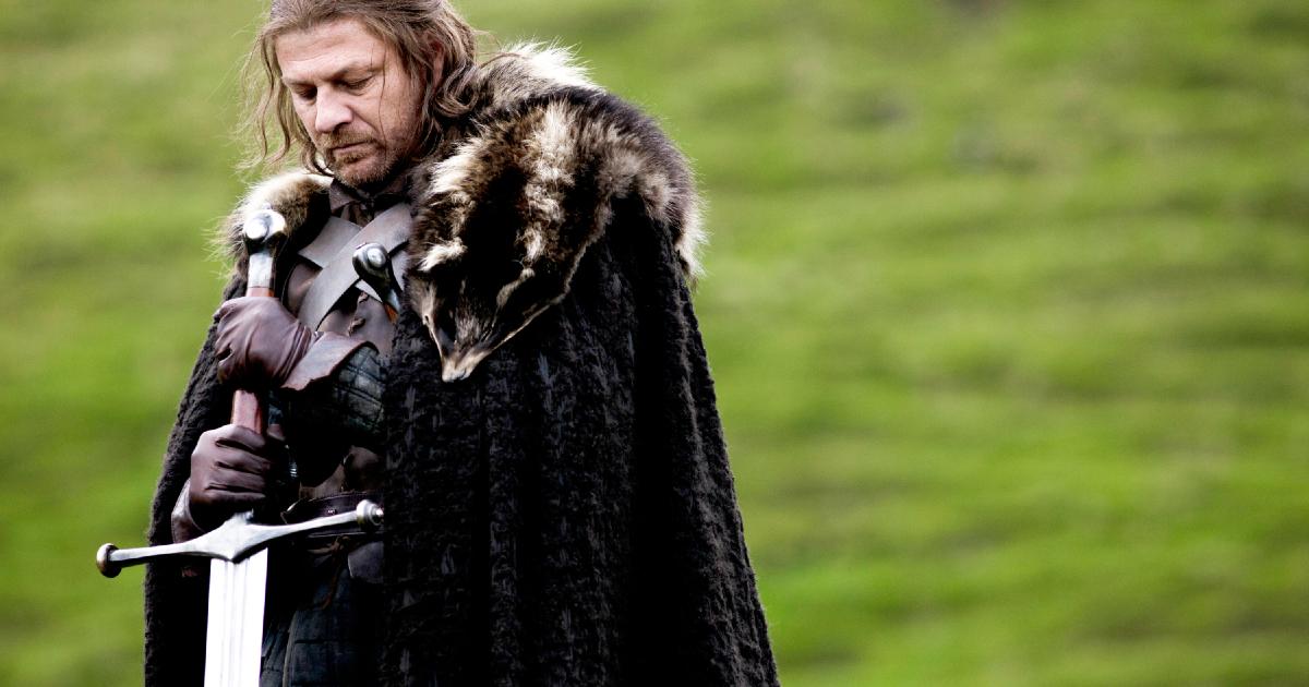Game of Thrones: Eddard Stark, con la sua enorme spada in mano mentre riflett ad occhi chiusi nel verde della prateria.