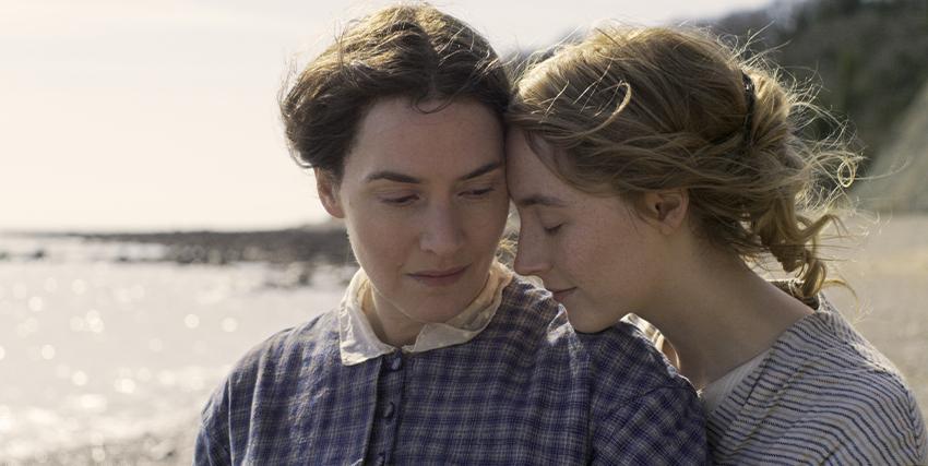 le due protagoniste di ammonite si sfiorano romanticamente su una spiaggia - nerdface