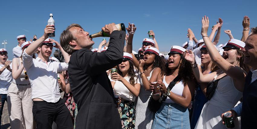 mads mikkelsen beve da una bottiglia di champoagna mentre tutti intorno a lui i presenti lo incitano - nerdface