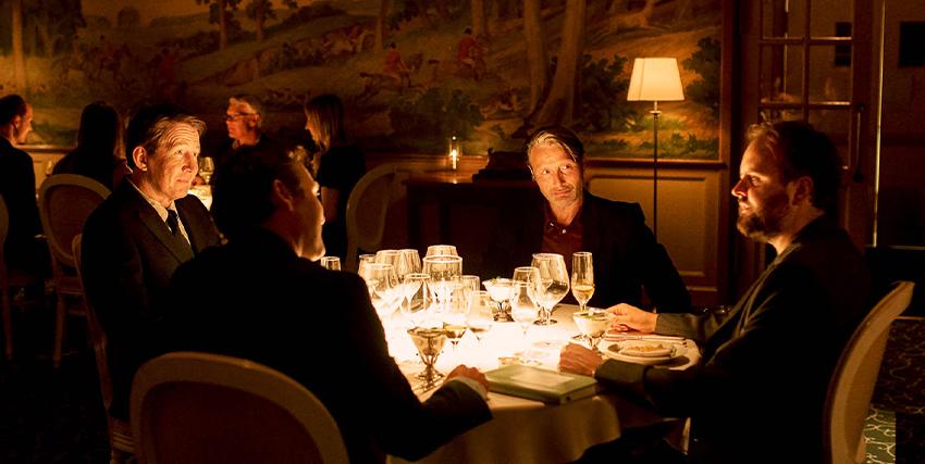 mads mikkelsen sorride mentre è a tavola con altri quattro uomini - nerdface