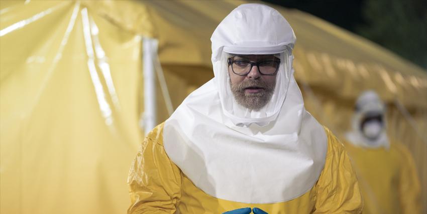 un uomo in tuta anti contaminazione è in piedi davanti a una tenda - nerdface