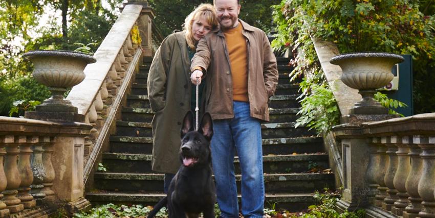 ricky gervais e la sua nuova amica passeggiano sorridenti insieme al cane nero di lui - nerdface