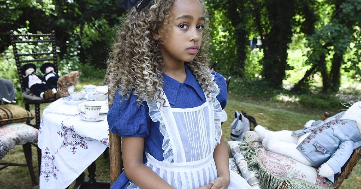 alice è nel suoi tipico vestito bianco e turchese, seduta a un tavolo in mezzo al bosco - nerdface