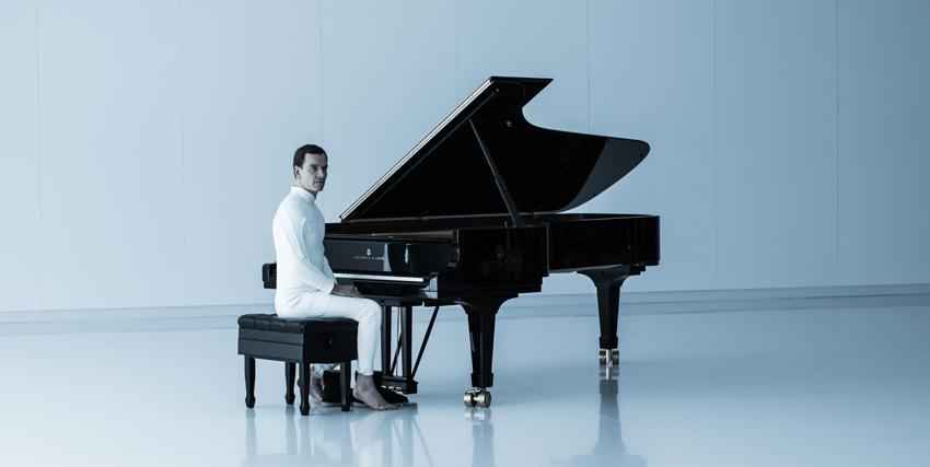 il sintetico interpretato da michael fassbender vestito di bianco è seduto al piano a coda posto al centro di una sala vuota - nerdface