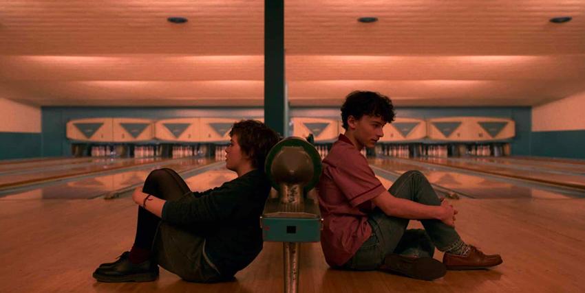 sophia lillis e un amico sono èpoggiati schiena contro shciena su un palo al centro di una pista da bowling - nerdface
