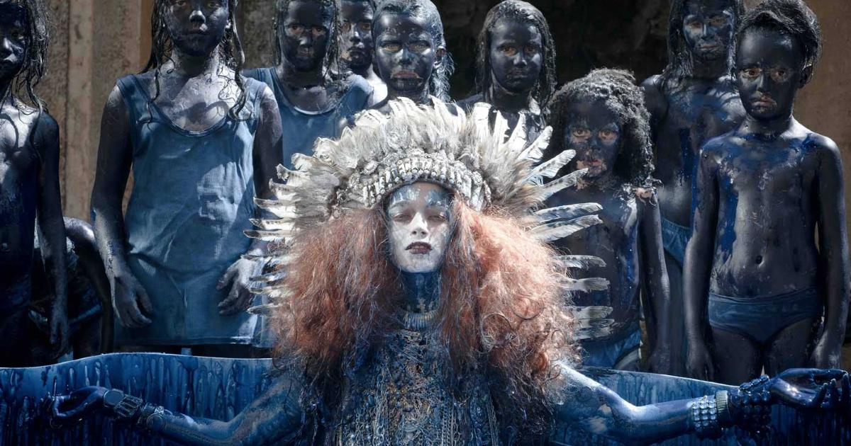 una banda di bambini tutti pitturati di blu petrolio, guidata da una leader col capo cinto da una corona di lunghe piume - nerdface