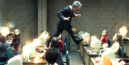 il protagonista cammina sopra le scrivanie dei suoi colleghi che lo guardano sorpresi - nerdface