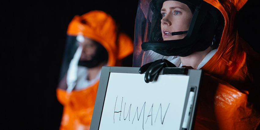 amy adams cerca di comunicare con gli alieni, indossandp una tuta aranbcione e tenendo in mano una lavagnetta con scritto human. un'immagine presa per migliaia di meme - nerdface
