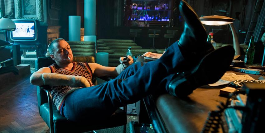 james mcavoy è seduto su una sedia imbottita e poggia i piedi sulla scrivania di fronte a lui - nerdface