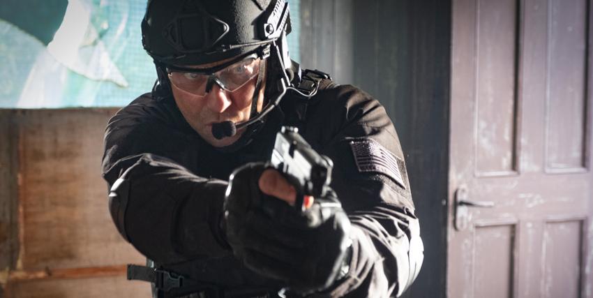 gerard butler indossa una divisa nera e punta la pistola in avanti durante un'esercitazione - nerdface