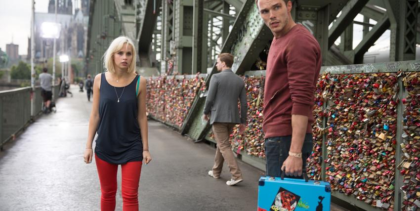 nicholas hoult tiene in mano una valigetta blu mentre si volta a guardare indietro su un ponte - nerdface