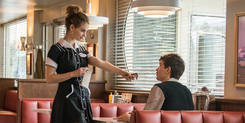 il protagonista sta parlando con una cameriera che lo sta servendo al tavolo: anche noi, come lui, ci innamoreremmo trattandosi di lily james - nerdface