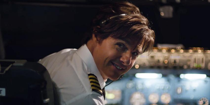 tom cruise si volta sul sedile di guida di un aereo di linea e sorride - nerdface