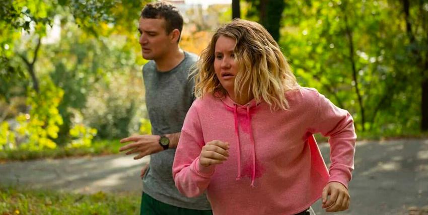 brittany sta correndo in una tuta rosa e faticosamente supera un ragazzo - nerdface