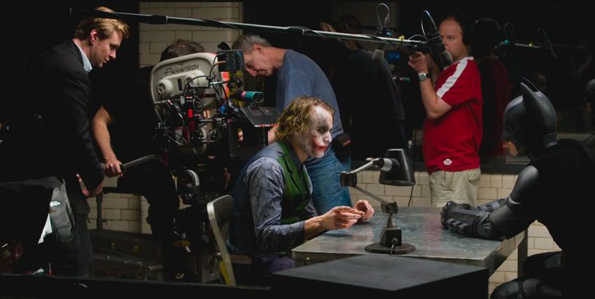 Christopher Nolan durante le riprese sul set de Il Cavaliere Oscuro con Joker e Batman al tavolo insieme - nerdface