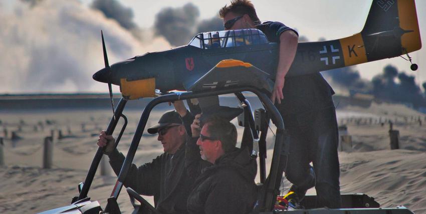 Christopher Nolan con un modellino di aereo sul set di Dunkirk - nerdface
